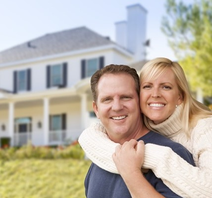 Happy couple with a restored home after water damaged