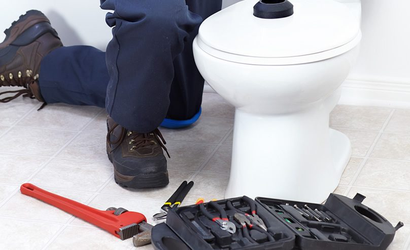 Contractor working on repair a toilet with sewage leak